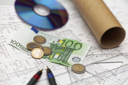 Money, ruler, dvd, tube and special pens lay down on an architect plan.