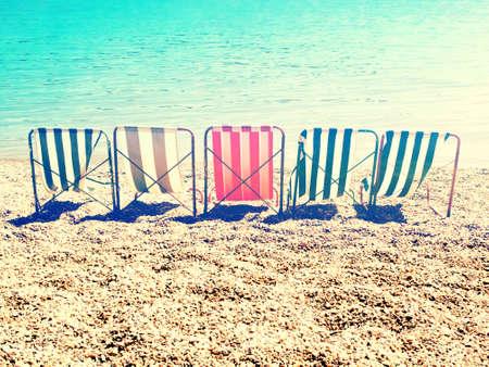 couple summer: chill on beach with retro stripes sun bed   cross processing style