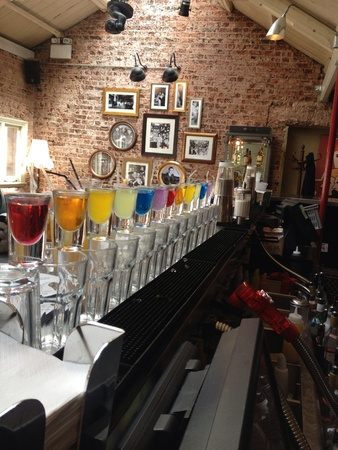 rainbow cocktail: Vodka shots lined up by colour in loft space