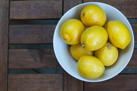 Fresh yellow lemons on the wooden table Stock Photo