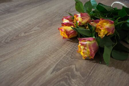 Fresh bouquet of rosses on the wooden background with some text space