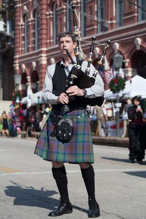 dickens: Galveston, TXUSA - 12 06 2014: Male musician in traditional Scottish costume plays harp at Dickens on the Strand Festival in Galveston, TX Editorial