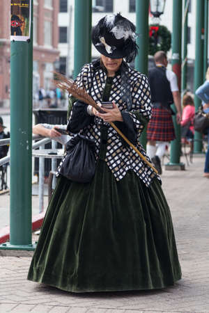 dickens: Galveston, TXUSA - 12 06 2014: Lady dressed in Victorian style texting on the phone at Dickens on the Strand Festival in Galveston, TX