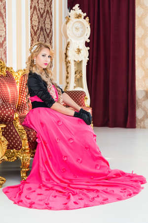 luxurious sofa: Stylish blonde in long red dress is sitting on luxurious sofa
