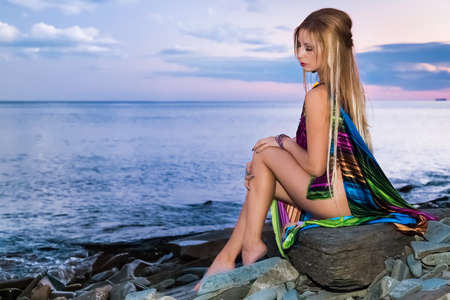 Attractive blonde is sitting on the beach at sunset
