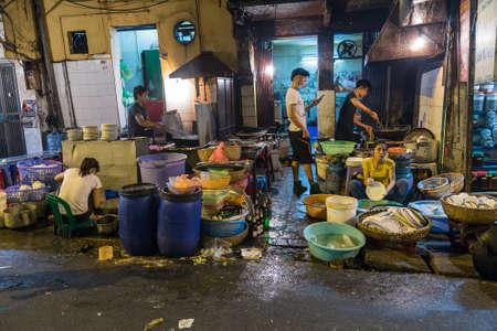 HANOI, VIETNAM - CIRCA AUGUST 2015: People make food in the street restaurant, Hanoi, Vietnam