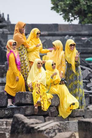 hijab: YOGYAKARTA, INDONESIA - CIRCA SEPTEMBER 2015: Women wearing hijab and yellow traditional dresses sit on the ruins of Prambanan temple Editorial