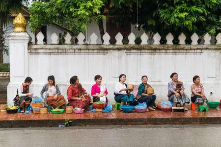 distributing: Luang Prabang, Laos - circa August 2015: Traditional Alms giving ceremony of distributing food to buddhist monks on the streets of Luang Prabang, Laos