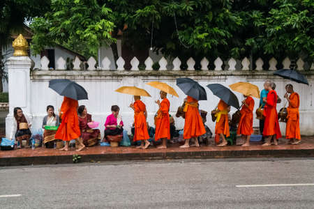 Luang Prabang, Laos - circa August 2015: Traditional Alms giving ceremony of distributing food to buddhist monks on the streets of Luang Prabang, Laos