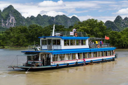 the mainland: Guilin, China - circa July 2015: Cruise boat sails between karst mountains and limestone peaks of Li river in China
