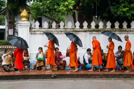 alms: Luang Prabang, Laos - circa August 2015: Traditional Alms giving ceremony of distributing food to buddhist monks on the streets of Luang Prabang, Laos
