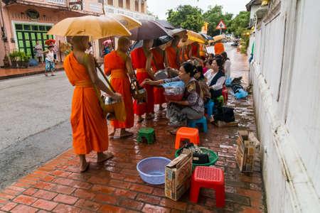 limosna: Luang Prabang, Laos - alrededor de agosto de 2015: Limosna tradicional ceremonia de entrega de la distribución de alimentos a los monjes budistas en las calles de Luang Prabang, Laos