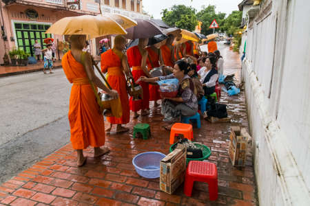 tradition: Luang Prabang, Laos - circa August 2015: Traditional Alms giving ceremony of distributing food to buddhist monks on the streets of Luang Prabang, Laos