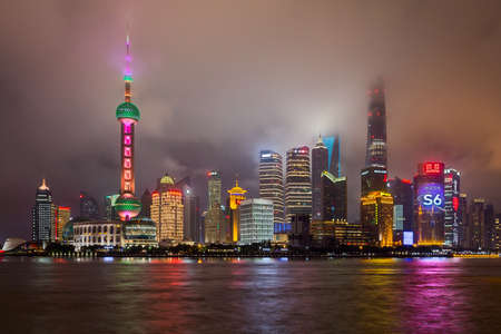 the mainland: Shanghai, China - circa September 2015: Skyline of Shanghai in clouds by night Editorial