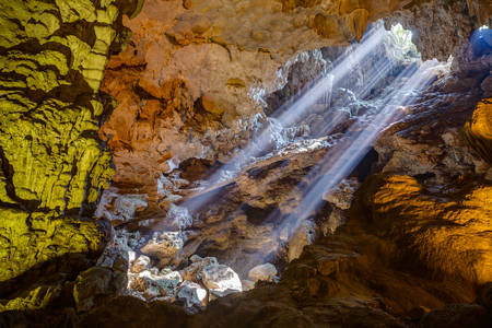 halong: Sun rays come through ceiling hole in Dau Go cave in Halong Bay