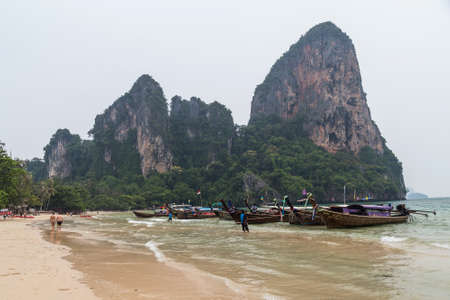 Krabi, Thailand - circa September 2015: Boats and limestone cliffs of Railay Beach in Krabi, Thailand