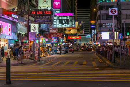 Hong Kong, China - circa September 2015: Streets of Hong Kong with pedestrians, lights and neon signs at night
