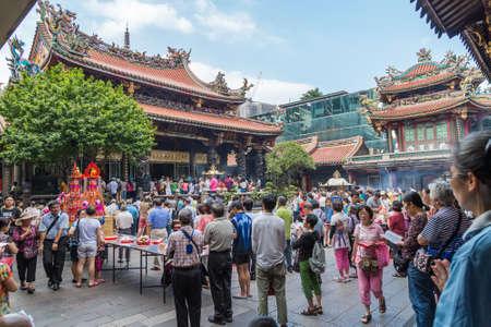 Taipei, Taiwan - circa September 2015: People pray in Longshan Buddhist temple in Taipei city, Taiwan 新聞圖片