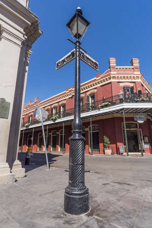 ironwork: New Orleans, LAUSA - circa February 2016: Pole with street signs and old Colonial House with ironwork galleries on the Streets of French Quarter decorated for Mardi Gras in New Orleans, Louisiana