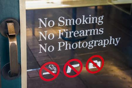 No Smoking, No Firearms, No Photography sign at the door entrance