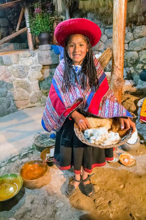Ollantaytambo, Peru - circa June 2015: Girl in traditional Peruvian clothes holds a basket with Alpaca and Llama wool near Cusco, Peru