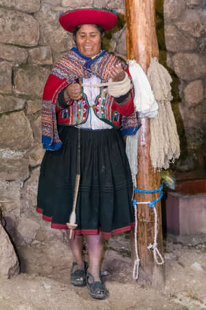 Ollantaytambo, Peru - circa June 2015: Woman in traditional Peruvian clothes makes yarn from Alpaca and Llama wool near Cusco, Peru
