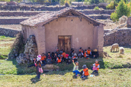 pisaq: Ollantaytambo, Peru - circa June 2015: Children in traditional Peruvian clothes are waiting for a schoold bus near Cusco, Peru Editorial