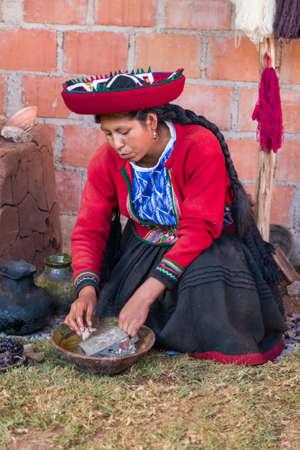 Ollantaytambo, Peru - circa June 2015: Woman in traditional Peruvian clothes uses natural dye for Alpaca and Llama wool near Cusco, Peru