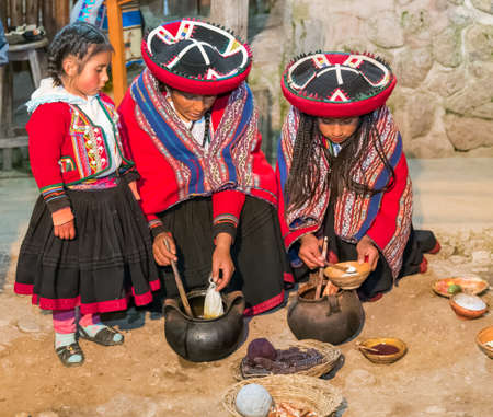kids weaving: Ollantaytambo, Peru - circa June 2015: Women in traditional Peruvian clothes use natural dyes for Alpaca and Llama wool near Cusco, Peru
