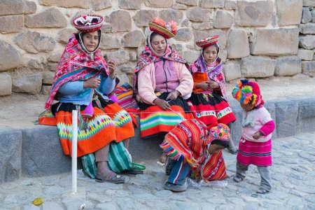 peru: Ollantaytambo, Peru - circa June 2015: Women and children in traditional Peruvian clothes in Ollantaytambo, Peru Editorial