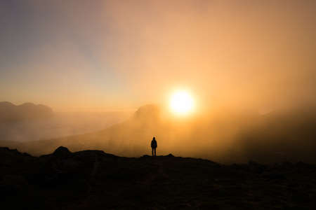 Hiker in awe of incredible Hornstrandir nature reserve illuminated by midnight sun Stock Photo