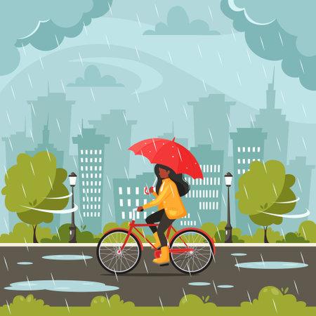 Black woman riding bike under an umbrella during the rain. Fall rain. Autumn outdoor activities.