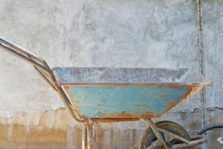 Old blue wheelbarrow on concrete  blocks wall background