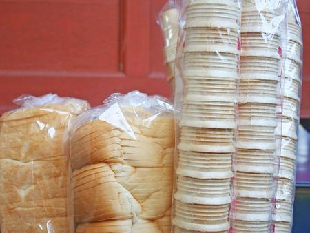 Lege roomijskornetten en brood in plastic zak