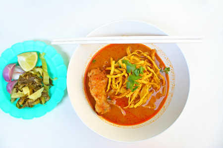 Egg Noodle in Chicken Curry and side dish which are pickles,lemon slices and shallots (Kao Soi Kai ) Stock Photo