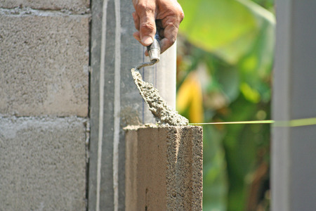 Bricklayer worker  installing cement blocks wall Imagens
