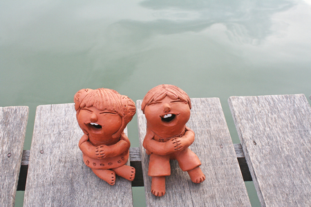 Laughing clay pottery dolls sitting on wood