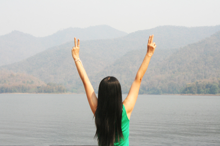 Asian woman  relaxing at the lake with mountain view in holiday trip