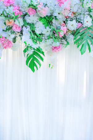 Colorful ornamental flowers group on white curtains with reflection from sunlight on background for wedding scene