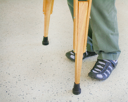 Man using wood crutches on terrazzo floor background