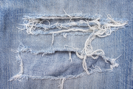 Texture blue jeans with ripped on background, hole and white threads destroyed patterns on denim