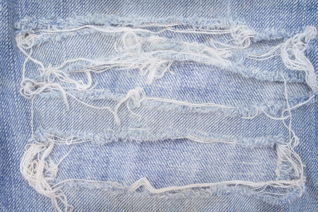 Blue jeans with ripped patterns for background, hole and white threads destroyed on denim