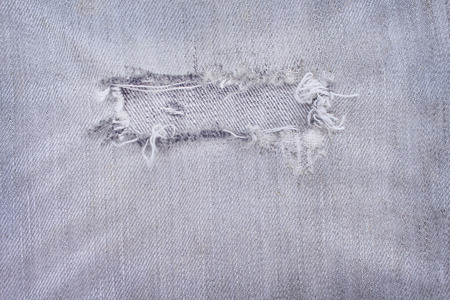 Light black jeans with ripped patterns texture for background, hole and white threads destroyed on denim