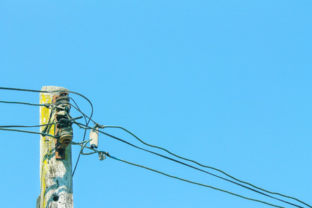 Low voltage power cable on old wood pole and clear blue sky background Stock Photo