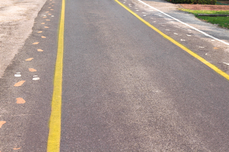 Asphalt road with two yellow lines and sidewalk mark  , white and Фото со стока