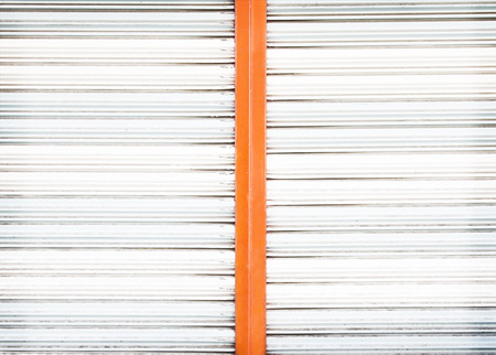 Old white and orange rolling steel door texture for background Banque d'images