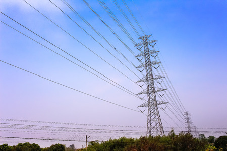 High voltage pole on blue sky with clouds background and landscape of rural