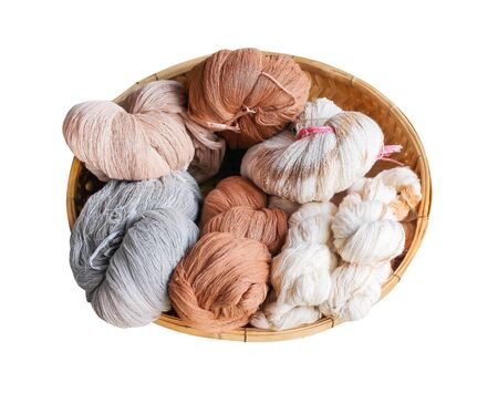 Multicolored raw cotton thread in wood tray isolated on white background