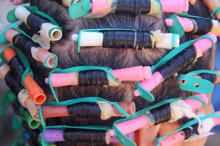 Asian elderly woman  head and colorful plastic rollers with hair perm solution , curling process background