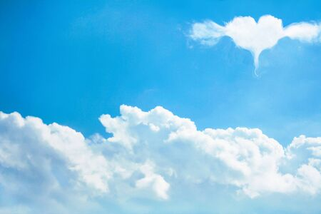 Landscape fluffy clouds group patterns and  heart shaped with wings concept floating on bright blue sky background , copy space 免版税图像